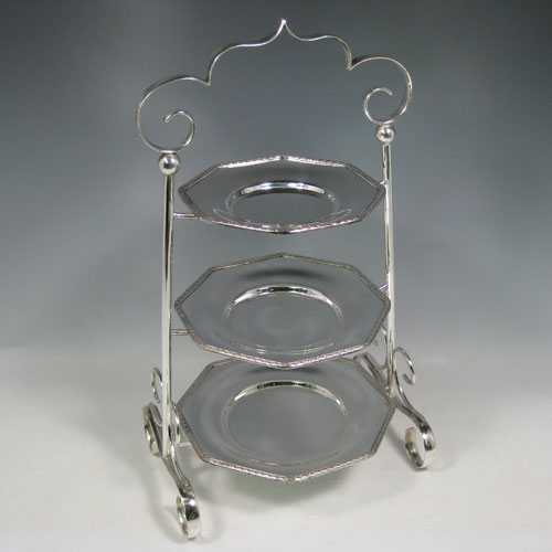 Antique Edwardian silver plated three-tier cake stand, having a graduated suite of three removable octagonal plates with applied leaf borders, sitting within a very pretty tapering frame with scroll-work handle and feet. Made by Frederick Atkins of Sheffield in ca. 1910. The dimensions of this fine hand-made silver-plated cake stand are height 38 cms (15 inches), width at base 22 cms (8.6 inches), width of largest plate 18 cms (7 inches), width of smallest plate 14 cms (5.5 inches).