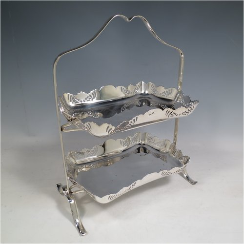 An Antique Edwardian pretty silver-plated cake stand, having two rectangular plates with hand-pierced floral borders, all held in a plain wire-work frame sat on four flanged feet. All made by Thomas Wilkinson of Sheffield in ca. 1900. The dimensions of this fine hand-made silver-plated cake stand are height 32 cms (12.5 inches), length 25.5 cms (10 inches), and width 16 cms (6.5 inchs).