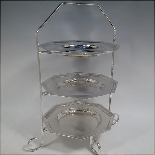 A very handsome Antique Edwardian silver plated three-tier cake stand, having a suite of three removable plain octagonal plates, sitting within a  frame with four scroll-work feet. Made in ca. 1910. The dimensions of this fine hand-made antique silver-plated cake stand are height 34 cms (13.3 inches), length at base 28 cms (11 inches), and width of plates 18 cms (7 inches).