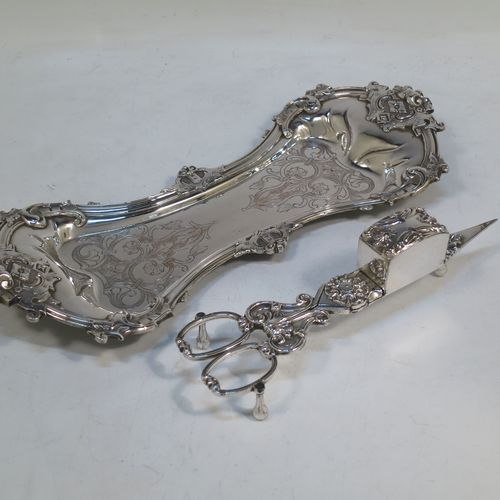 An Antique Georgian Old Sheffield Plated candle scissor snuffer stand and candle scissor snuffer, the stand having an applied floral & scroll border, a hand-chased ground with floral decoration, and sitting on a flat base with four stud feet. The scissor snuffer with matching decoration and all in original working condition. Made in ca. 1830. The dimensions of this fine hand-made antique Old Sheffield Plated snuffer stand and scissors are length 26 cms (10.25 inches), and width 11 cms (4.25 inches),