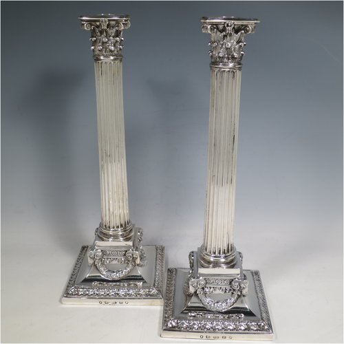 An Antique Victorian Sterling Silver pair of large table candlesticks, in a Neoclassical Corinthian style having square bases with hand-chased floral borders, applied rams heads and laurel-leaf swags, with fluted columns and acanthus-leaf capitals, and removable nozzles. Made by Frederick Elkington of Birmingham in 1873. The dimensions of this fine pair of hand-made antique silver candlesticks are height 31 cms (12.25 inches), and bases 11.5 cms (4.5 inches) square.