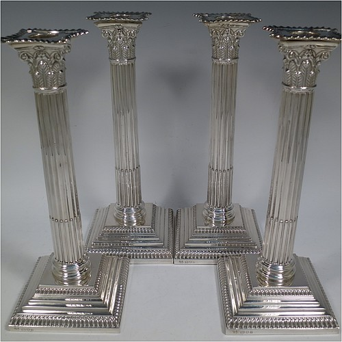 A very handsome set of four Sterling Silver table candlesticks, in a Neoclassical Corinthian style having square stepped bases, fluted columns, acanthus leaf capitals, removable nozzles, and gadroon borders. Made by D and J Welby of London in 1936. The dimensions of this fine hand-made set of four silver candlesticks are height 26 cms (10.25 inches), and their bases are 10 cms (4 inches) square.