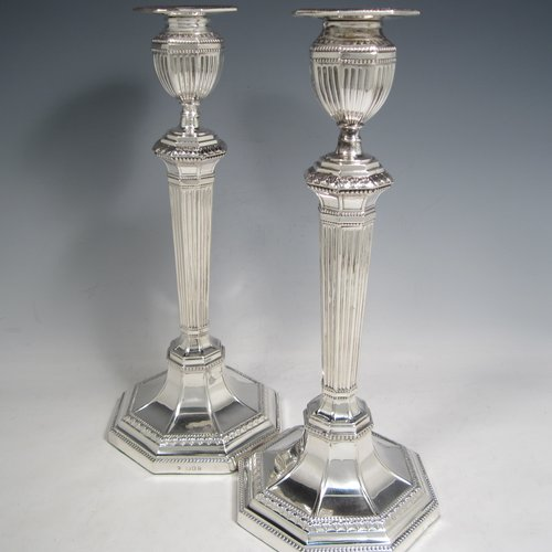 Sterling silver pair of large table candlesticks, in a Neoclassical style, having octagonal baluster bodies with hand-chased fluted decoration, with bead borders and bands of floral work, tapering columns, and removable nozzles. Made by Franz Schiebner London in 1919. The dimensions of these fine hand-made silver candlesticks are height 32 cms (12.5 inches), and width at bases 13.5 cms (5.3 inches).