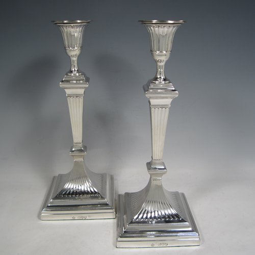 An Antique Victorian Sterling silver pair of large table candlesticks, in a Neoclassical style, having square cross-section bodies with hand-chased fluted decoration, tapering columns, and removable nozzles. Made by William Hutton of London in 1893. The dimensions of these fine hand-made silver candlesticks are height 30.5 cms (12 inches), and 12 cms (4.75 inches) square at bases.