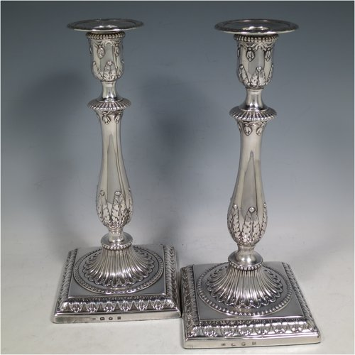 An Antique Georgian sterling silver pair of candlesticks, having round baluster bodies with hand-chased anthemion leaf and fluted decoration, with bead-edged borders, sitting on square bases with matching decoration, and original removable nozzles. These are made in Sheffield in 1776 which is very early for this town as the first assay mark was in 1773. The dimensions of these fine hand-made antique Georgian silver candlesticks are height 27 cms (10.5 inches), base 12 cms (4.75 inches) square.