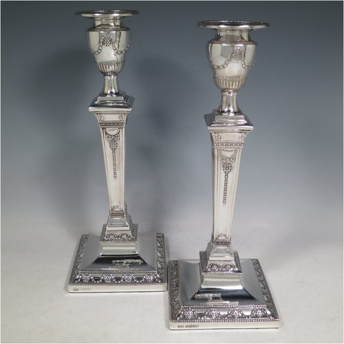 An Antique Victorian Sterling Silver pair of large table candlesticks, in a Neoclassical style, having square cross-section bodies with hand-chased swags and garland decoration, tapering columns, removable nozzles, and bead-edged borders. Made by J. K. Bembridge of Sheffield in 1886. The dimensions of these fine hand-made silver candlesticks are height 28 cms (11 inches), and 11 cms (4.25 inches) square at bases.