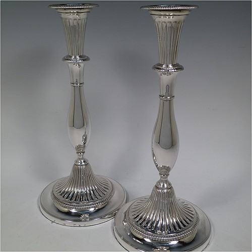 An Antique Georgian Sterling Silver pair of candlesticks, having round bellied bodies with hand-chased fluted decoration, with gadroon borders, and removable nozzles. Made by John Green, Roberts, Mosley and Co., of Sheffield in 1800. The dimensions of these fine hand-made antique silver candlesticks are height 30 cms (11.75 inches), diameter of bases 13.5 cms (5.3 inches) diameter. Please note that these candlesticks are filled.