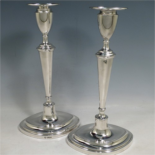 An Antique Sterling Silver pair of candlesticks, having plain oval neoclassical style boat-shaped bodies with reeded borders, and removable nozzles. Made by Hawksworth, Eyre and Co. Ltd., of Sheffield in 1916. The dimensions of these fine hand-made silver table candlesticks are height 30.5 cms (12 inches), and width at base 16 cms (6.25 inches).