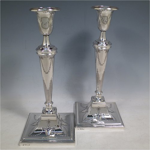 A Sterling Silver pair of large table candlesticks, in a Neoclassical style having square bases and round tapering columns, with hand-chased floral swags, ribbon bows, and fluted decoration, together with reeded borders and removable nozzles. Made by Hawksworth Eyre & Co., of Sheffield in 1919. The dimensions of this fine pair of hand-made large silver candlesticks are height 29 cms (11.5 inches), and bases 12 cms (4.75 inches) square.