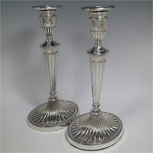 A Sterling Silver very pretty pair of large table candlesticks, in a neoclassical Adams style, having oval bodies with tapering columns and hand-chased inverted flute decoration, with applied bead-edged borders, and removable nozzles. Made by D. J. Silver of London in 1963. The dimensions of these fine hand-made silver candlesticks are height 29 cms (11.5 inches), and length at bases 15 cms (6 inches).