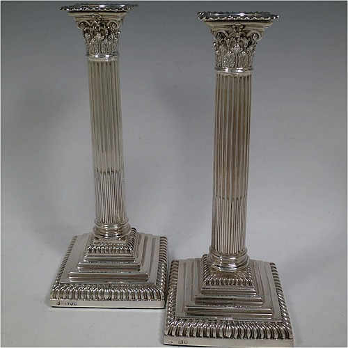 A very handsome and bold pair of Antique Victorian Sterling Silver table candlesticks, in a Neoclassical Corinthian style having square stepped bases, fluted columns, acanthus leaf capitals, removable nozzles, and gadroon borders. Made by Gibson and Langland of London in 1895. The dimensions of this fine hand-made pair of antique silver candlesticks are height 28 cms (11 inches), and their bases are 11.5 cms (4.5 inches) square.