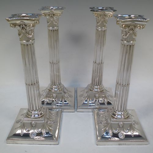A very handsome set of four Antique Victorian Silver Plated table candlesticks, in a Neoclassical Corinthian style having square stepped bases with swag and lion-mask decoration, fluted columns, laurel leaf swag capitals, removable nozzles, and bead-edged borders. Made by Hawksworth Eyre and Co., of Sheffield in ca. 1880. The dimensions of this fine hand-made set of four antique silver-plated candlesticks are height 26 cms (10.25 inches), and their bases are 11 cms (4.3 inches) square.