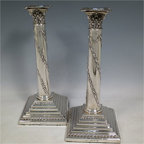 An Antique Georgian Sterling Silver pair of table candlesticks, in a Neoclassical style having square stepped bases with gadroon borders, the columns with swirled garlands of flowers, scroll capitals with anthemion leaves, and removable nozzles. Made by John Winter & Co., of Sheffield in 1776. The dimensions of these fine hand-made antique silver candlesticks are height 28 cms (11 inches), and the bases are 12 cms (4.75 inches) square.