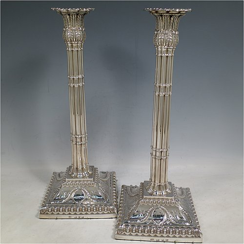An Antique Georgian Sterling Silver pair of table candlesticks, in a Neoclassical style having square bases with bead borders, hand-chased floral swags and male head motifs, the columns in a bound palm-tree style with frond capitals, and removable nozzles. Made by John Cox of London in 1771. The dimensions of these fine antique silver candlesticks are height 32 cms (12.5 inches), bases 12.5 cms (5 inches) square. Please note that these candlesticks are crested.