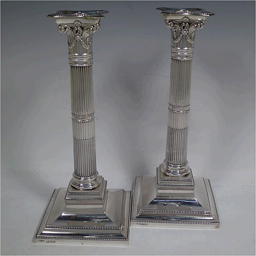 A very pretty pair of Sterling Silver table candlesticks, in a Neoclassical Corinthian style having square stepped bases, fluted columns, swag style capitals, removable nozzles, and bead-edged borders. Made by Mappin and Webb of London in 1935, and Sheffield in 1928. The dimensions of this fine hand-made pair of silver candlesticks are height 26 cms (10.25 inches), and their bases are 11.5 cms (4.5 inches) square.