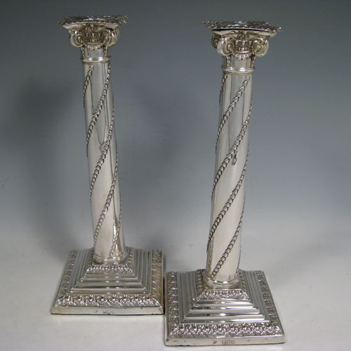 Antique Victorian sterling silver pair of table candlesticks, in a Neoclassical style having square stepped bases with hand-chased floral work, the columns with swirled garlands of flowers, scroll capitals with swags, and removable nozzles with gadroon borders. Made by William Hutton of London in 1901. Height 27.5 cms (10.75 inches), bases 11 cms (4.25 inches) square.