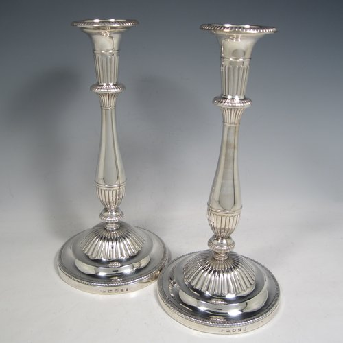 Antique Georgian sterling silver pair of candlesticks, having round baluster bodies with hand-chased fluted decoration, with gadroon borders, and removable nozzles. Made by Nathaniel Smith & Co., of Sheffield in 1803/04. The dimensions of these fine hand-made silver candlesticks are height 30 cms (11.75 inches), base 14 cms (5.5 inches) diameter. Please note that these candlesticks are filled and have wooden insert bases.