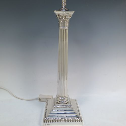 A large and very handsome Sterling Silver candlestick that has been converted to an electric table lamp, in a Neoclassical Corinthian style, having a square stepped base with gadroon borders, a fluted column, and an acanthus leaf capital. Made by Hawksworth, Eyre and Co., of Sheffield in 1927. The dimensions of this fine hand-made silver electric table lamp candlestick are height 47 cms (18.5 inches), and the base is 14 cms (5.5 inches) square. Please note that this table lamp has been fitted with a system that will work with a 240v supply, and including a UK style three-pin plug.