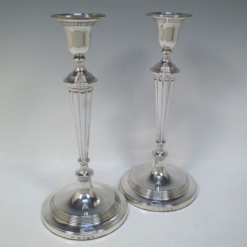 A very handsome pair of Antique Georgian Sterling Silver large table candlesticks in a Neoclassical style, having round bodies with hand-chased reeded borders, tapering columns with hand-chased fluting, and original removable nozzles. Made by John Green and Son Ltd., of Sheffield in 1796. The dimensions of this fine hand-made pair of antique silver candlesticks are height 30 cms (11.75 inches), and diameter at bases 13.5 cms (5.3 inches).