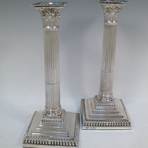 A very handsome pair of Antique Victorian Sterling Silver table candlesticks, in a Neoclassical Corinthian style having square stepped bases, fluted columns, acanthus leaf capitals, removable nozzles, and gadroon borders. Made by Hawksworth, Eyre and Co., of Sheffield in 1893. The dimensions of this fine hand-made pair of antique silver candlesticks are height 28 cms (11 inches), and their bases are 11 cms (4.3 inches) square.