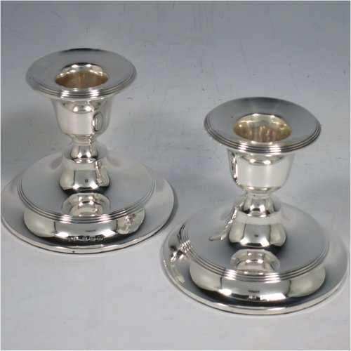 An Antique Edwardian Sterling Silver pair of candlesticks, in a very plain round style, having baluster bodies with hand-chased reeded borders. Made by Henry Matthews of Birmingham in 1904. The dimensions of these fine hand-made silver candlesticks are height 7 cms (2.75 inches), and the bases are 8 cms (3.25 inches) diameter.