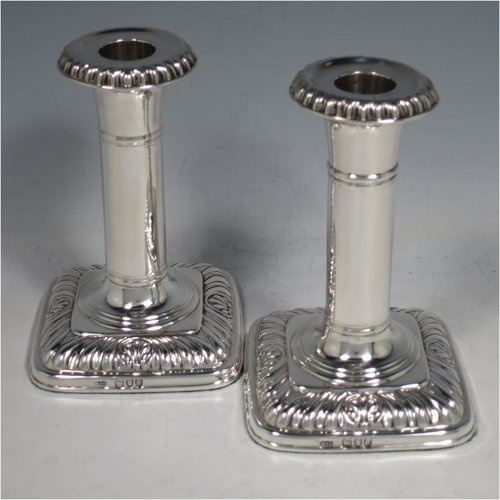 An Antique Victorian Sterling Silver pair of candlesticks, in a Georgian Regency style with plain round columns on square bases with rounded corners, gadroon edged borders, and removable nozzles. Made by Matthew John Jessop of London in 1895. The dimensions of this fine pair of hand-made silver candlesticks are height 14 cms (5.5 inches), and the bases are 9 cms (3.5 inches) square.