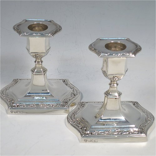 An Antique Edwardian Sterling Silver very pretty pair of small candlesticks, having shaped rectangular bodies, with hand-chased floral borders, and removable nozzles. Made by Hawksworth & Eyre ltd., of Sheffield in 1902. The dimensions of these fine hand-made antique silver candlesticks are height 10 cms (4 inches), and the bases are 10 cms (4 inches) long, by 7.5 cms (3 inches) wide.