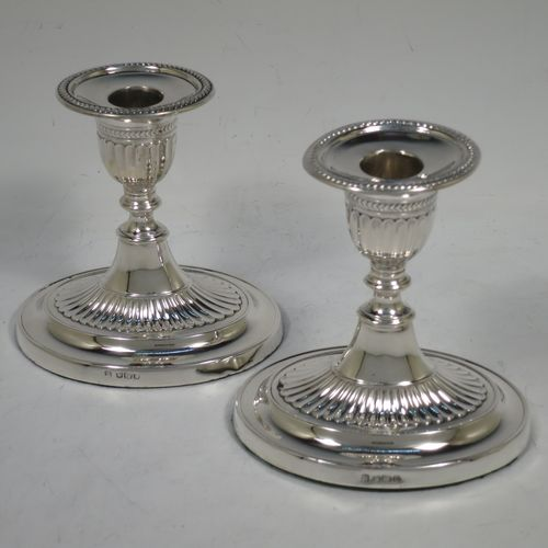A very pretty pair of Antique Edwardian Sterling Silver candlesticks, having oval bodies with hand-chased half-fluted decoration, original removable nozzles with applied leaf-style borders. Made by Fordham and Faulkner of Sheffield in 1906. The dimensions of these fine hand-made antique silver candlesticks are height 11 cms (4.25 inches), and the bases are 11 cms (4.25 inches) long.