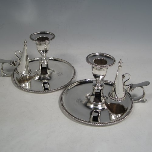 An Antique Georgian Sterling Silver pair of chamber-sticks, having plain round bodies, removable nozzles, original dunce-cap snuffers, and applied gadroon-edged borders. Made by Daniel Smith & Robert Sharp of London in 1788. The dimensions of these fine hand-made silver chambersticks are height 9 cms (3.4 inches), diameter 14 cms (5.5 inches), and they weigh a total of approx. 580g (18.7 troy ounces). Please note that both items are crested.