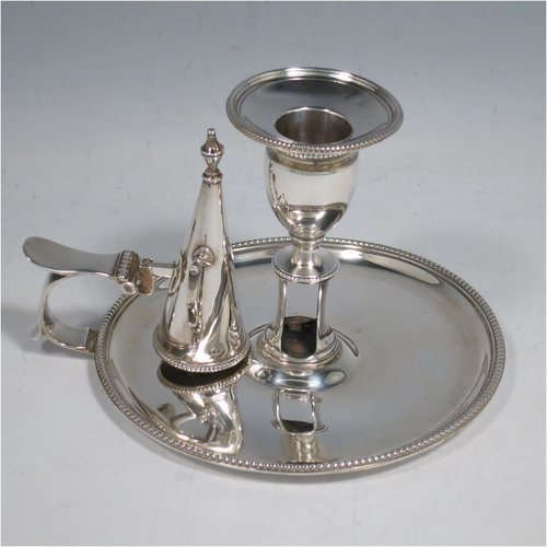 An Antique Georgian Sterling Silver chamber-stick, having a round base, a handle with thumb-piece, an original removable dunce-cap extinguisher, an original removable nozzle, and with applied bead-edged borders. Made by John Crouch & Thomas Hannam of London in 1782. The dimensions of this fine hand-made silver chamberstick are diameter 13.5 cms (5.3 inches), height 10 cms (4 inches), and it weighs approx. 245g (7.9 troy ounces).