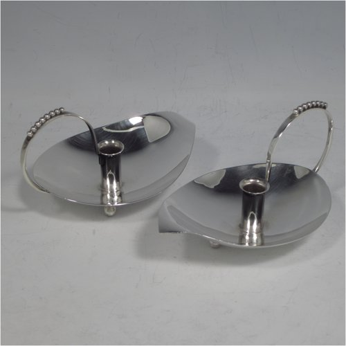 A Sterling Silver modernistic style pair of small chamber-sticks for taper candles, having plain leaf-form bodies, scroll handles with applied bead-work, and sitting on three ball feet. Made by A. E. Jones of Birmingham in 1960. The dimensions of these fine hand-made silver chambersticks are length 11 cms (4.25 inches), width 7 cms (2.75 inches), height 6 cms (2.3 inches), and they weigh a total of approx. 98g (3.2 troy ounces).