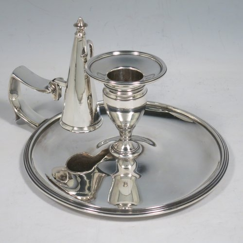 An Antique Georgian Sterling Silver chamber-stick, having a round base, a cast plain scroll handle, an original removable dunce-cap extinguisher, an original removable nozzle, and with applied reed-edged borders. Made by Samuel & George Whitford of London in 1806. The dimensions of this fine hand-made antique silver chamberstick are diameter 13.5 cms (5.25 inches), height 9.5 cms (3.75 inches), and it weighs approx. 326g (10.5 troy ounces).