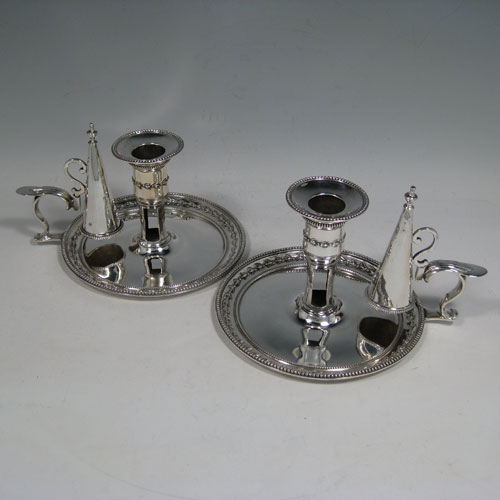 Antique Georgian sterling silver pair of chambersticks, having round bodies with bead and floral borders, scroll handles with removable dunce-cap extinguishers, and removable bobeches. Made by Elizabeth and Robert Jones of London in 1781 and 1784. Height 9.5 cms (3.75 inches), diameter 14 cms (5.5 inches). Total weight approx. 500g (16 troy ounces).