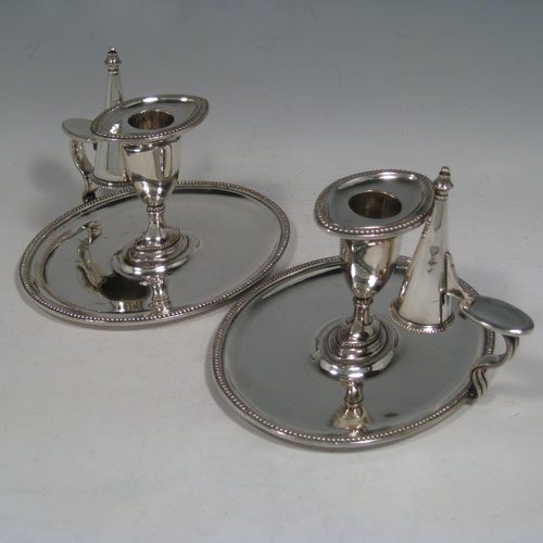 Antique Georgian pair of Old Sheffield plated chambersticks, having plain oval bodies, removable nozzles, original dunce-cap snuffers, and bead-edged borders. Made in ca. 1790. The dimensions of these fine hand-made Old Sheffield plated chambersticks are height 11 cms (4.3 inches), length 16 cms (6.25 inches), and width 14 cms (5.5 inches).
