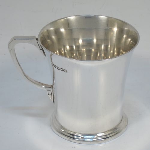 A very handsome Art Deco style Sterling Silver christening mug, having a plain round body with tapering sides, a scroll handle, and sitting on a pedestal foot with reeded decoration. Made by Mappin and Webb of Sheffield in 1934. The dimensions of this fine hand-made Art Deco silver christening mug are height 7 cms (2.75 inches), length 9 cms (3.5 inches), and it weighs approx. 115g (3.7 troy ounces).