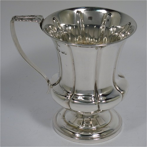 An Antique Georgian Sterling Silver christening mug, having a round bellied body, with hand-chased melon style fluted decoration, an acanthus leaf scroll handle, and sitting on a pedestal foot. Made by William Bateman of London in 1829. The dimensions of this fine hand-made antique silver christening mug are height 11 cms (4.3 inches), length 11.5 cms (4.5 inches), and it weighs approx. 185g (6 troy ounces).