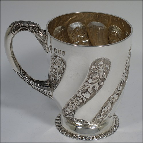 An Antique Victorian Sterling Silver christening mug, having a round bellied body with tapering sides and alternate hand-chased floral and plain swirl fluted decoration, a cast foliate scroll handle, and all sitting on a collet foot with an applied egg and dart border. Made by Gibson and Langland of London in 1893. The dimensions of this fine hand-made antique silver christening mug are height 10 cms (4 inches), diameter at lip 7.5 cms (3 inches), and it weighs approx. 175g (5.6 troy ounces).
