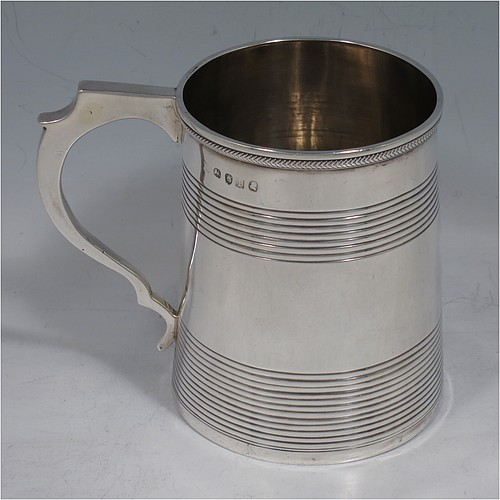 An Antique Georgian Sterling Silver christening mug, having a plain round body with two bands of hand-chased reeded decoration, an applied rope-twist top border, a scroll handle, and sitting on a flat base. Made in London in 1814. The dimensions of this fine hand-made antique silver christening mug are height 9 cms (3.5 inches), length 10 cms (4 inches), and it weighs approx. 129g (4.2 troy ounces).
