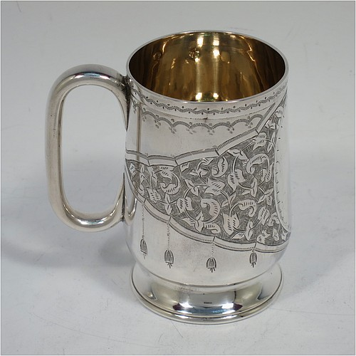 A very pretty Antique Victorian Sterling Silver christening mug, having a round body with straight tapering sides and tucked under belly, with hand-engraved floral and scroll-work decoration, a vacant oval cartouche, a plain loop handle, a gold-gilt interior, and all sitting on a pedestal foot. Made by Hilliard and Thomason of Birmingham in 1888. The dimensions of this fine hand-made antique silver christening mug are height 8.5 cms (3.3 inches), diameter at lip 5.5 cms (2.25 inches), and it weighs approx. 119g (3 troy ounces).
