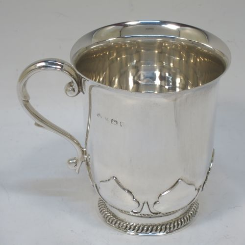 A handsome and unusual Sterling Silver christening mug, having a plain round body and tucked under belly with applied cut-card work, a scroll handle, and sitting on a pedestal foot with a gadroon or rope-twist border. Made by the Aie Brothers of Birmingham in 1924. The dimensions of this fine hand-made silver christening mug are height 9 cms (3.4 inches), length 10 cms (4 inches), and it weighs approx. 215g (7 troy ounces).