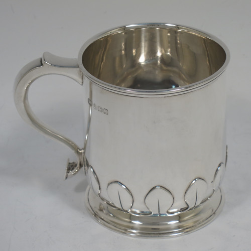 A handsome and unusual Sterling Silver christening mug, having a plain round body with tapering sides and tucked under belly with applied cut-card work, a scroll handle, and sitting on a pedestal foot. Made by Alexander Clarke of Birmingham in 1922. The dimensions of this fine hand-made silver christening mug are height 8 cms (3.25 inches), length 11 cms (4.25 inches), and it weighs approx. 200g (6.5 troy ounces).