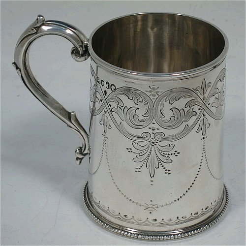 A very pretty Antique Victorian Sterling Silver christening mug, having a round body with straight sides, with hand-engraved floral and scroll decoration, applied bead-edged borers, a scroll handle, and sitting on a flat base. Made by the Alexander Macrae of London in 1864. The dimensions of this fine hand-made antique silver christening mug are height 9.5 cms (3.75 inches), diameter at lip 6.5 cms (2.5 inches), and it weighs approx. 157g (5 troy ounces).