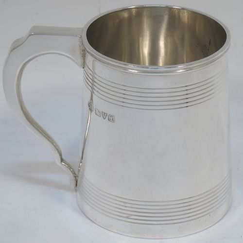 A very elegant Sterling Silver Georgian style christening mug, having a plain round body with two bands of hand-chased reeded decoration, a scroll handle with flat top, and sitting on a flat base. Made by Jays of Oxford Street, London in 1923. The dimensions of this fine hand-made silver christening mug are height 8 cms (3 inches), length 10 cms (4 inches), and it weighs approx. 160g (5.2 troy ounces).