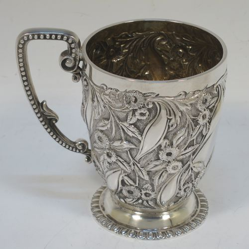 A beautiful Art Nouveau Antique Victorian Sterling Silver christening mug, having a round body with tapering sides, all hand-chased with floral and leaf-work decoration, a central vacant cartouche, a scroll handle with bead border, a gold-gilt interior, and all sitting on a pedestal foot. Made by Wakely and Wheeler of London in 1894. The dimensions of this fine hand-made antique art nouveau silver christening mug are height 10 cms (4 inches), diameter at lip 7 cms (2.75 inches), and it weighs approx. 163g (5.3 troy ounces).