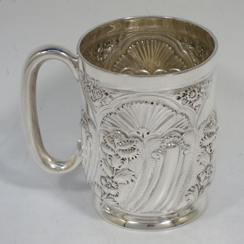 A very pretty Antique Victorian Sterling Silver christening mug, having a round straight-sided body with tucked under belly, all hand-chased with  floral and scroll-work decoration, a central vacant half-moon style cartouche, a plain loop handle, and all sitting on a collet foot. Made by George Maudsley Jackson of London in 1892. The dimensions of this fine hand-made antique silver christening mug are height 9.5 cms (3.75 inches), diameter at lip 7 cms (2.75 inches), and it weighs approx. 149g (4.8 troy ounces).