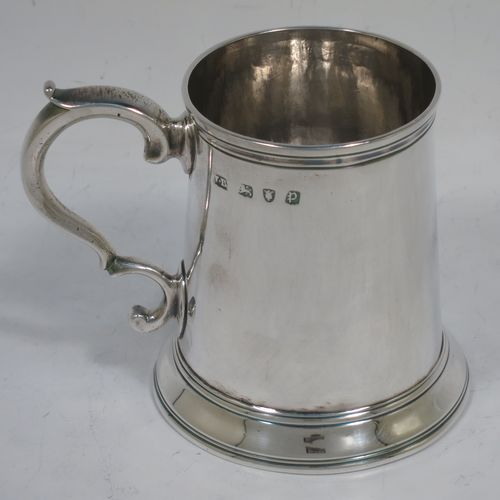 A very handsome Antique Georgian Sterling Silver christening mug, having a plain round body with applied reeded borders, a scroll handle, and sitting on a collet foot. Made by Walter Brind of London in 1770. The dimensions of this fine hand-made antique silver christening mug are height 9 cms (3.5 inches), length 11 cms (4.25 inches), and it weighs approx. 175g (5.6 troy ounces).