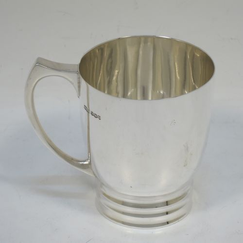 A very handsome Art Deco style Sterling Silver christening mug, having a plain round body with tapering sides, a scroll handle, and sitting on a pedestal foot with banded decoration. Made by James Dixon and Sons of Sheffield in 1938. The dimensions of this fine hand-made Art Deco silver christening mug are height 8 cms (3.25 inches), length 9 cms (3.5 inches), and it weighs approx. 165g (5.3 troy ounces).