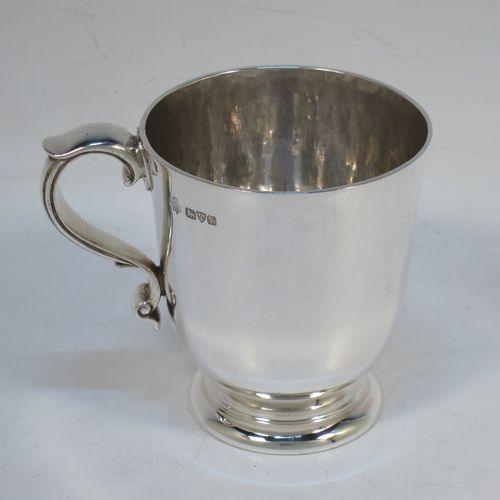 A handsome and heavy Antique Edwardian Sterling Silver christening mug, having a plain round straight-sided body with tucked under belly, a hand-hammered interior, a scroll handle with hand-chased reeded decoration, and sitting on a pedestal foot. Made by Jays of Chester in 1909. The dimensions of this fine hand-made antique silver christening mug are height 8 cms (3 inches), length 9.5 cms (3.75 inches), and it weighs approx. 161g (5.2 troy ounces).