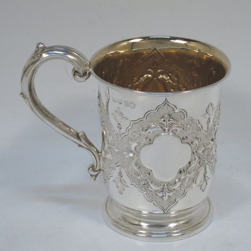 A very pretty Antique Victorian Sterling Silver christening mug, having a round body with straight tapering sides and tucked under belly, with hand-chased floral and scroll-work decoration surrounding four vacant lobed cartouches, a scroll loop handle, a gold-gilt interior, and all sitting on a pedestal foot. Made by Robert Hennell of London in 1865. The dimensions of this fine hand-made antique silver christening mug are height 10 cms (4 inches), diameter at lip 7 cms (2.75 inches), and it weighs approx. 130g (4.2 troy ounces).