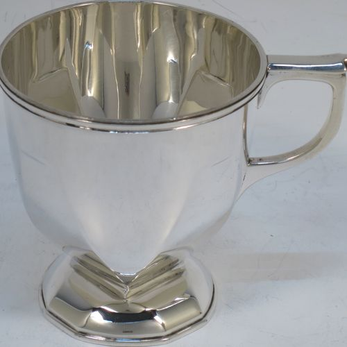 A very handsome Art Deco style Sterling Silver christening mug, having a plain round body with tapering sides and panelled decoration, a scroll handle, and sitting on a matching pedestal foot. Made by Northern Goldsmiths of Birmingham in 1931. The dimensions of this fine hand-made Art Deco silver christening mug are height 8 cms (3.25 inches), length 10 cms (4 inches), and it weighs approx. 113g (3.6 troy ounces).